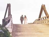 man-and-woman-holding-hands-while-walking-on-bridge-1048029